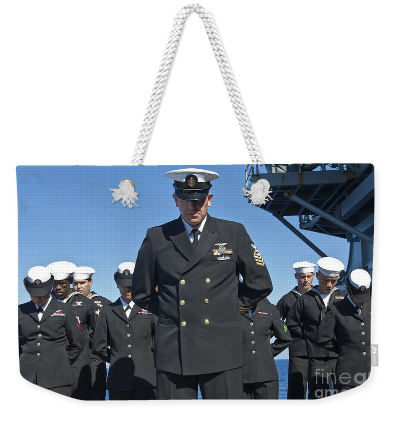 Military Weekender Tote Bag featuring the photograph A Prayer Is Delivered During A Burial by Stocktrek Images