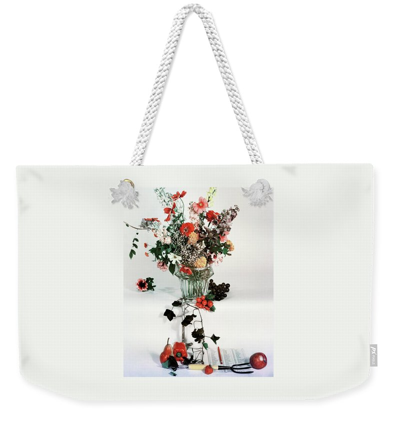 Nobody Weekender Tote Bag featuring the photograph A Studio Shot Of A Vase Of Flowers And A Garden by Herbert Matter