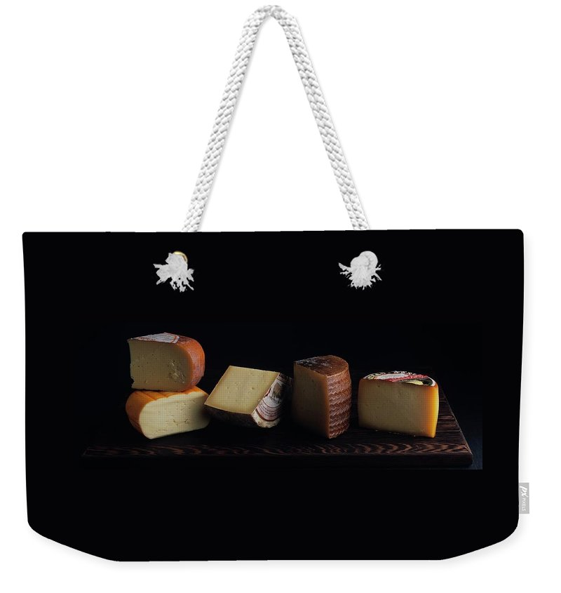 Dairy Weekender Tote Bag featuring the photograph A Variety Of Cheese On A Cutting Board by Romulo Yanes