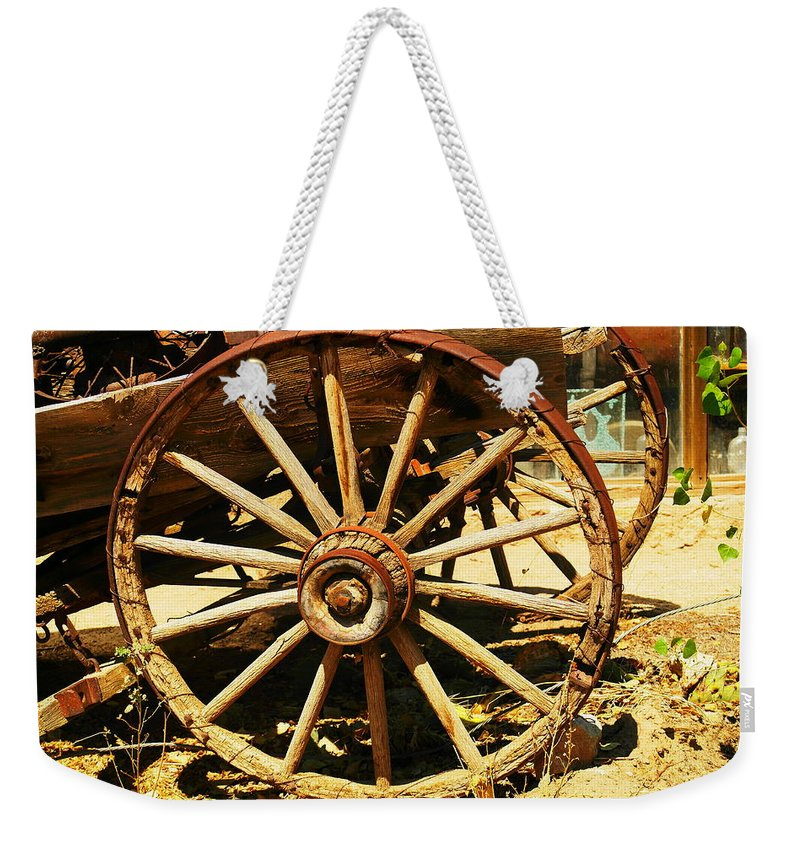 Rounds Weekender Tote Bag featuring the photograph A Wagon Wheel by Jeff Swan