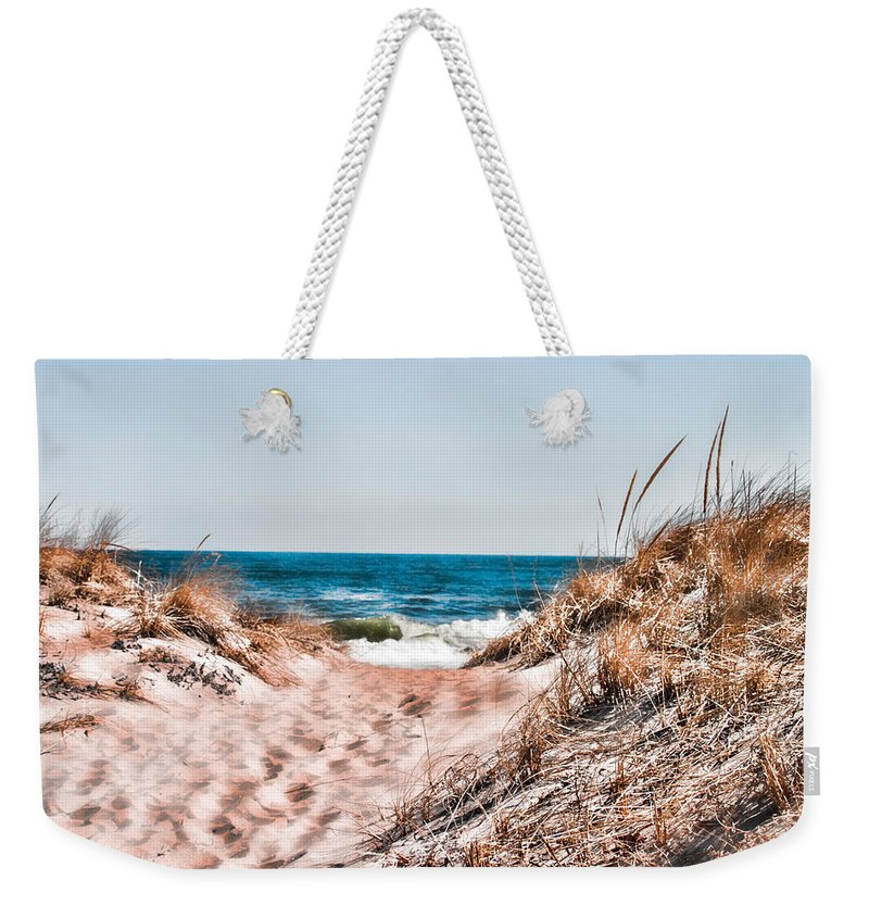 Beach Retaining Fence Weekender Tote Bag featuring the photograph A Walk Out To The Water by Jeff Folger