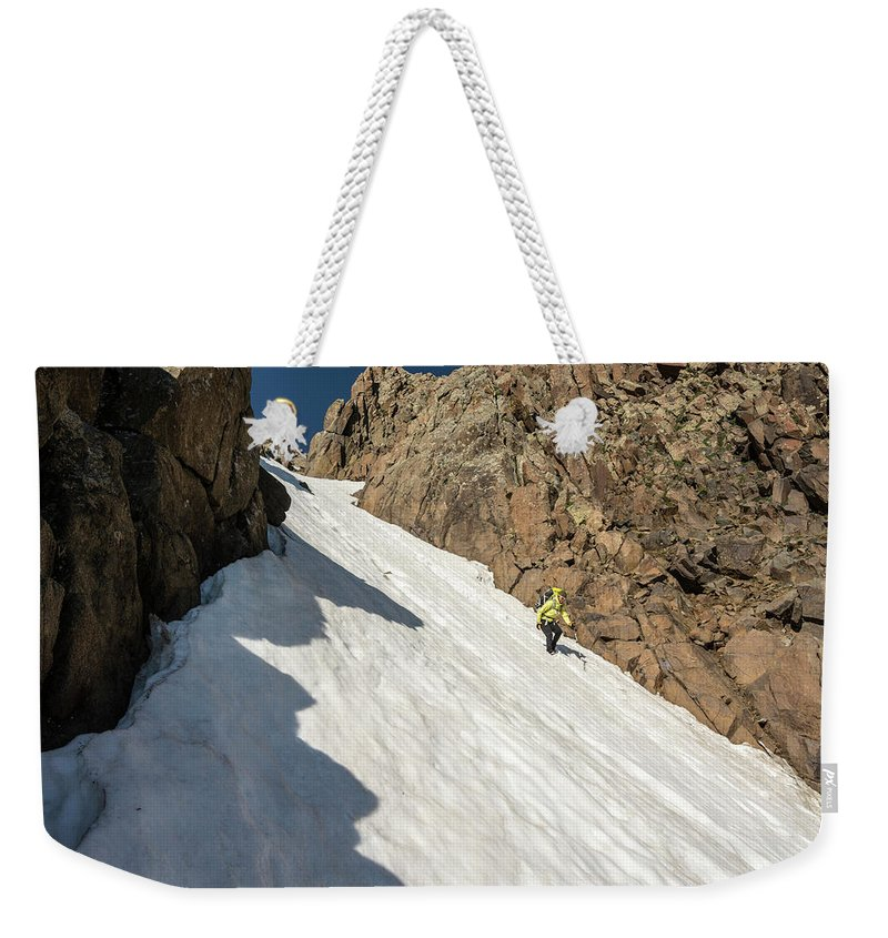 Low Angle View Weekender Tote Bag featuring the photograph A Woman Descending A Snow Slope While by Kennan Harvey