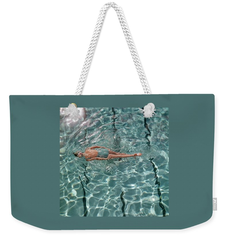 Water Weekender Tote Bag featuring the photograph A Woman Swimming In A Pool by Fred Lyon