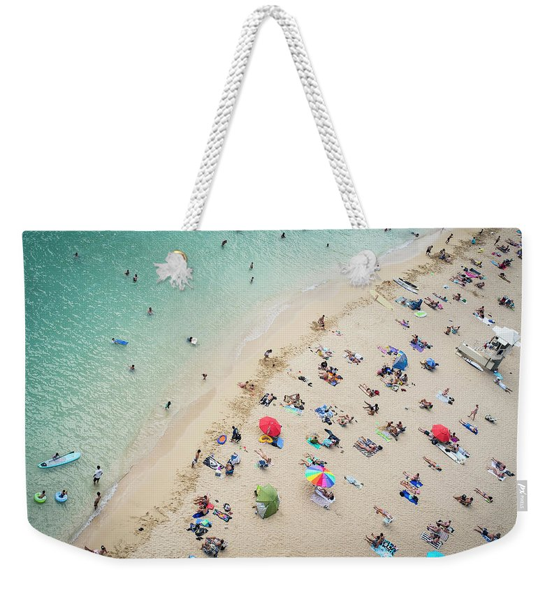 Honolulu Weekender Tote Bag featuring the photograph Aerial View Of Tourists On Beach by Alberto Guglielmi