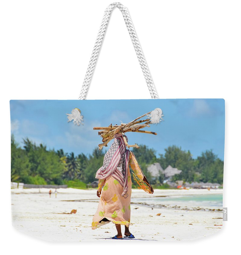 People Weekender Tote Bag featuring the photograph African Girl With A Bundle Of Reeds On by Volanthevist