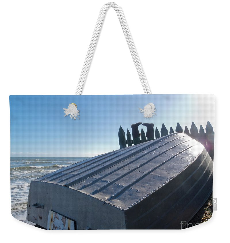 Aluminum Weekender Tote Bag featuring the photograph Aluminum Fishing Boat And Boots Drying On Fence by Stephan Pietzko