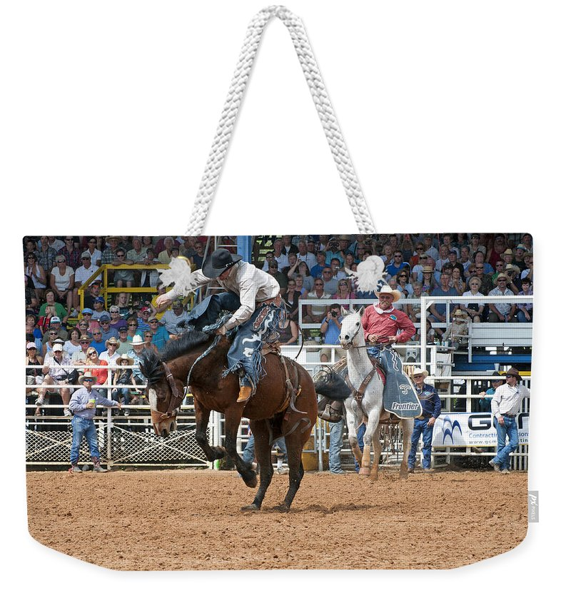 Rodeo Weekender Tote Bag featuring the photograph American Cowboy Riding Bucking Rodeo Bronc II by Sally Rockefeller