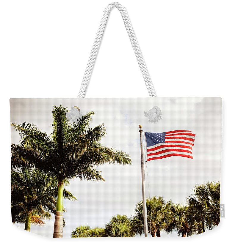 Tranquility Weekender Tote Bag featuring the photograph American Flag Flying Amongst Palm Trees by Ron Levine