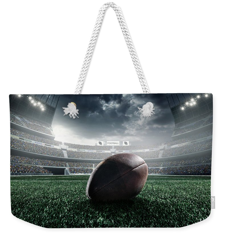 Event Weekender Tote Bag featuring the photograph American Football Ball by Dmytro Aksonov