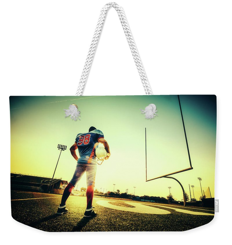 Headwear Weekender Tote Bag featuring the photograph American Football Player by Ferrantraite