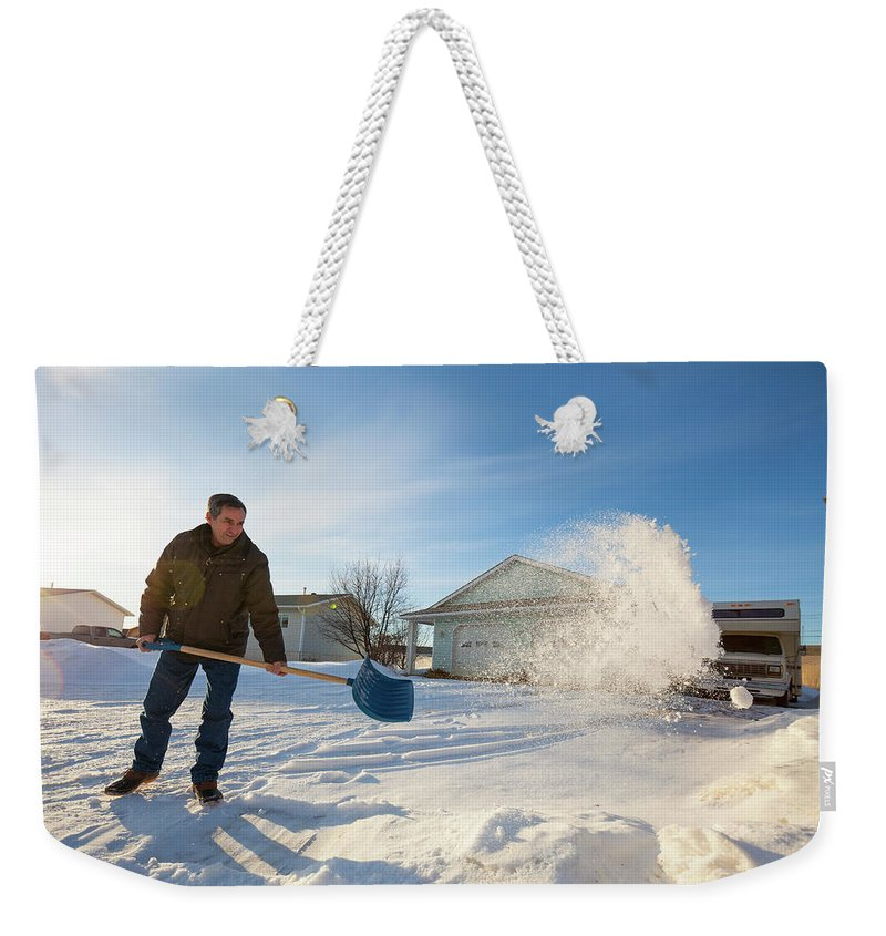 Cold Temperature Weekender Tote Bag featuring the photograph An Elderly Man Shovels Snow In Northern by Christopher Kimmel