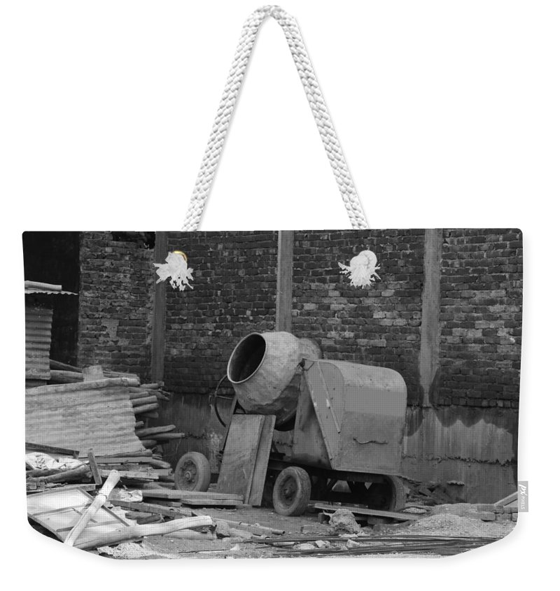 Brick Wall Weekender Tote Bag featuring the photograph An Old Cement Mixer And Construction Material by Ashish Agarwal