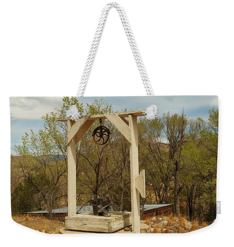 Water Weekender Tote Bag featuring the photograph An Old Well In Lincoln City New Mexico by Jeff Swan