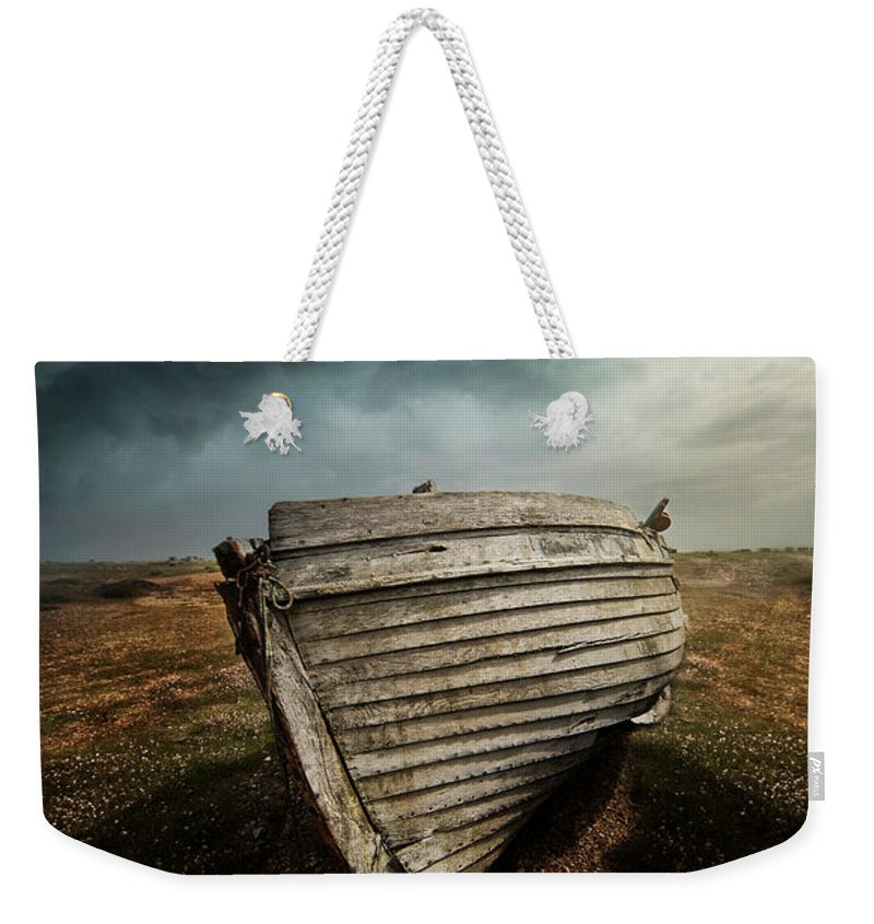 Boat Weekender Tote Bag featuring the photograph An Old Wreck On The Field. Dramatic Sky In The Background by Jaroslaw Blaminsky