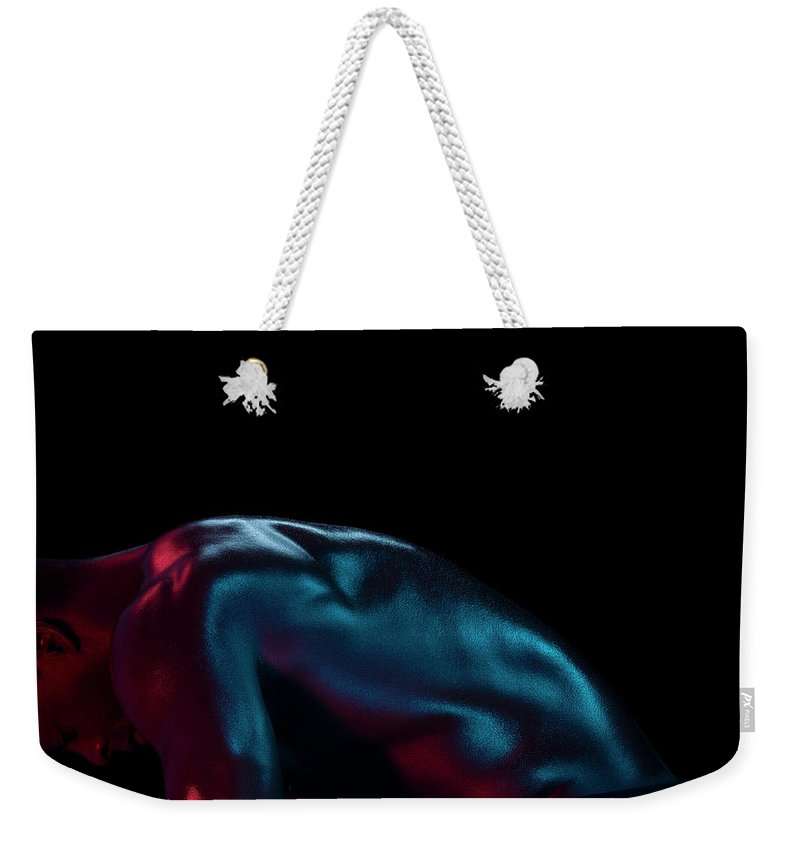 Cool Attitude Weekender Tote Bag featuring the photograph Athletic Male Bending, Head Down, Side by Jonathan Knowles