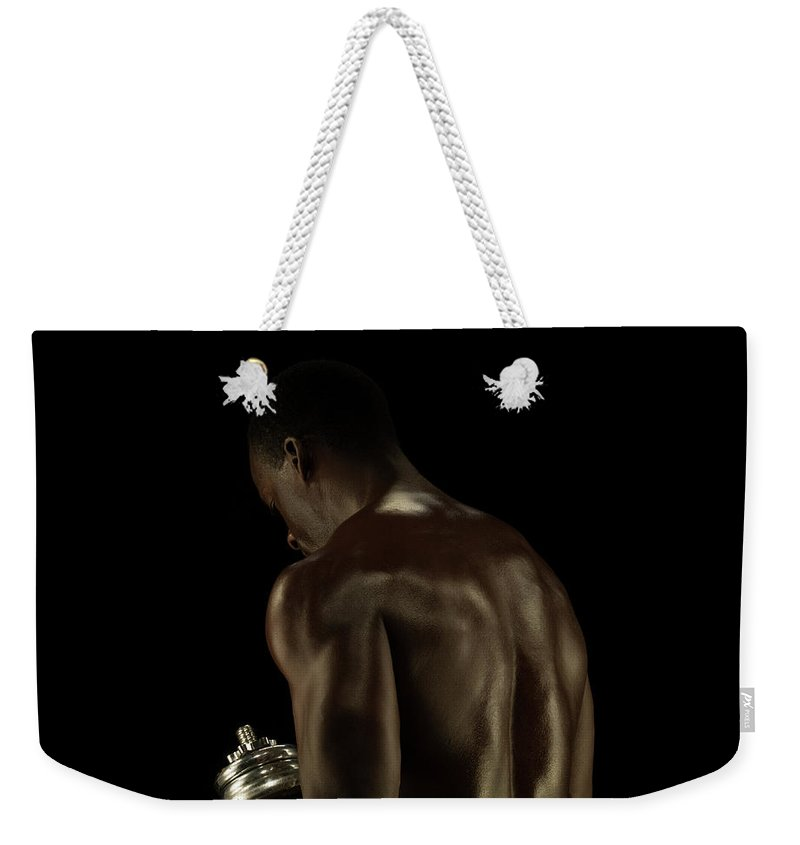 Mature Adult Weekender Tote Bag featuring the photograph Athletic Male Exercising With A Hand by Jonathan Knowles