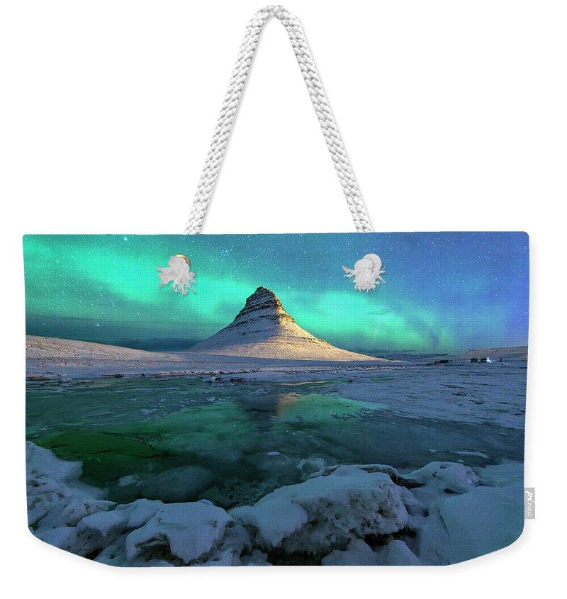 Tranquility Weekender Tote Bag featuring the photograph Aurora Over Kirkjufell Mountain Iceland by Ratnakorn Piyasirisorost
