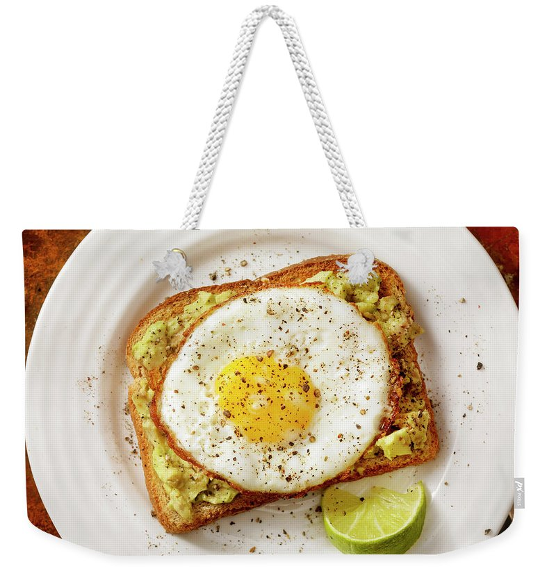 Breakfast Weekender Tote Bag featuring the photograph Avocado Toast With A Fried Egg by Lauripatterson