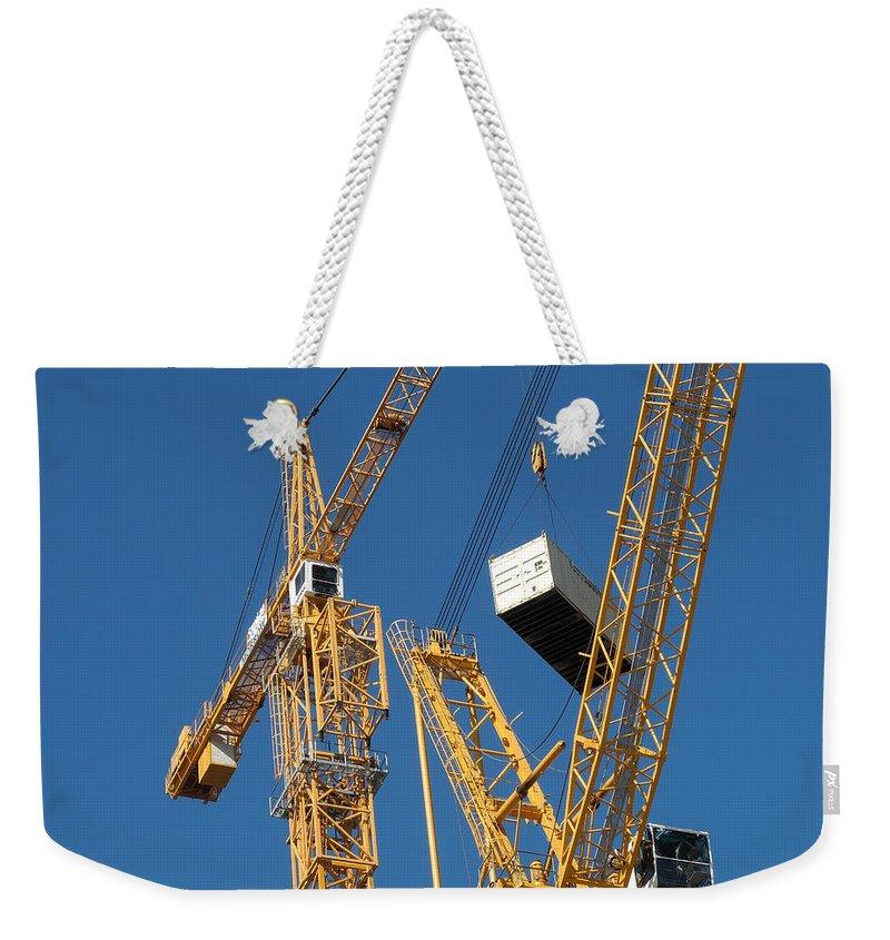 Construction Cranes Weekender Tote Bag featuring the photograph Balancing Act by Robert VanDerWal