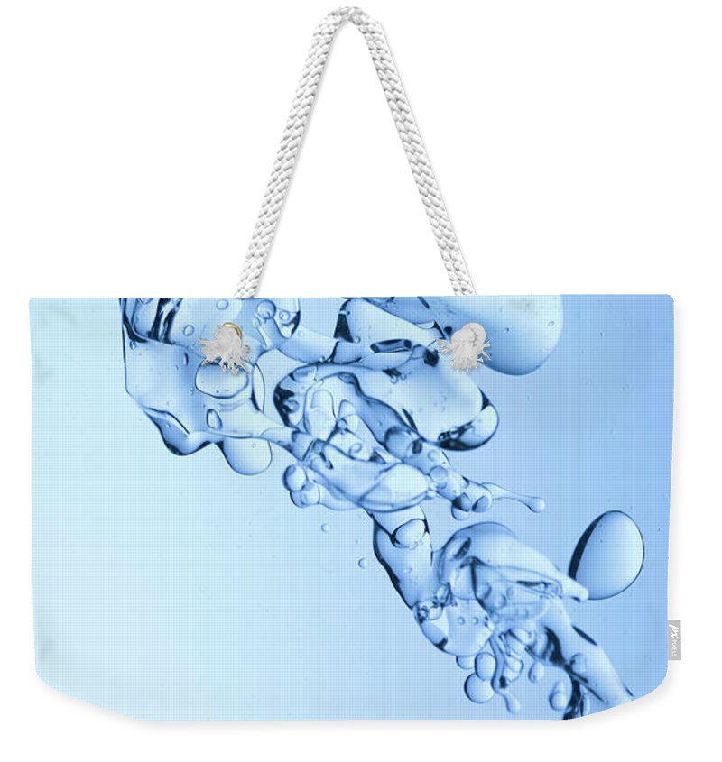 Yellow Weekender Tote Bag featuring the photograph Blue Oil Water Background by Grafissimo