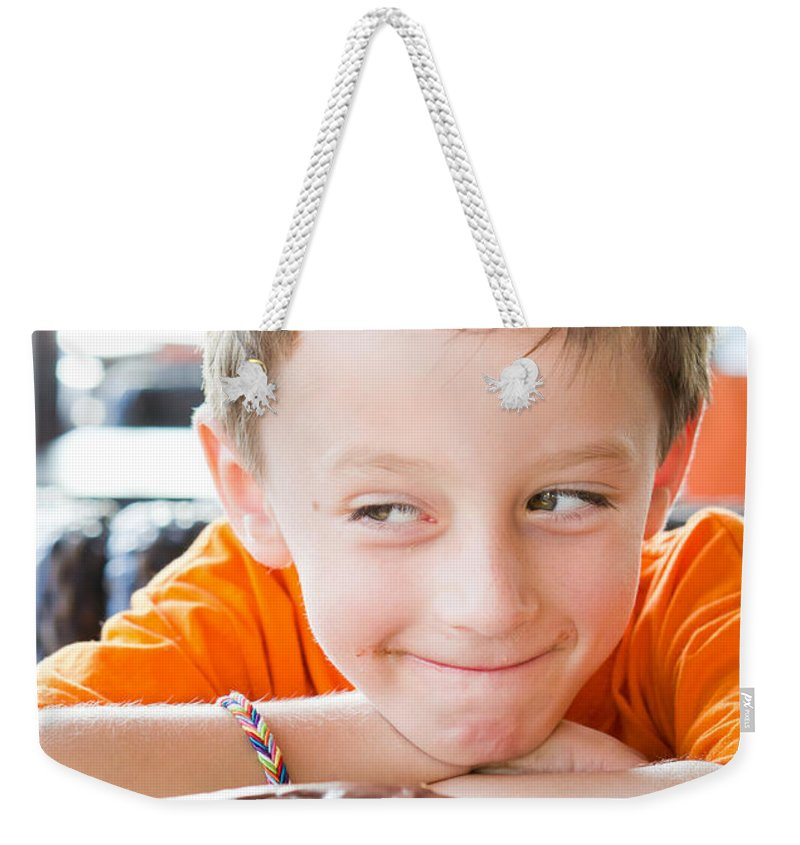Arms Weekender Tote Bag featuring the photograph Boy With Donut by Tom Gowanlock