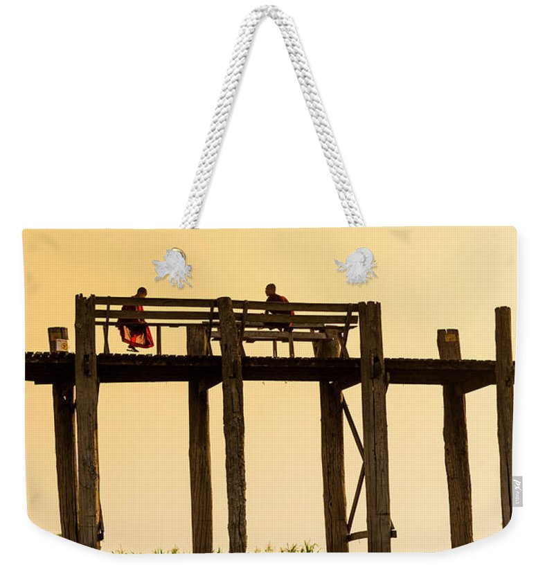 Grass Weekender Tote Bag featuring the photograph Buddhist Monks Seated On U Bein Bridge by Merten Snijders