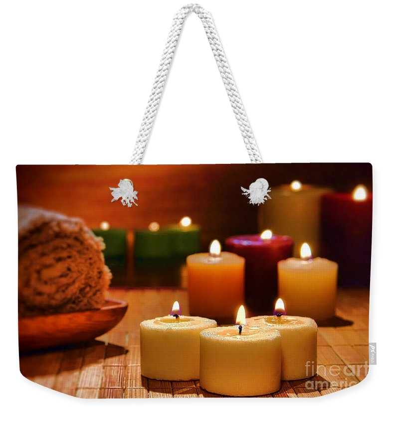 Candles Weekender Tote Bag featuring the photograph Candles Burning In A Spa by Olivier Le Queinec