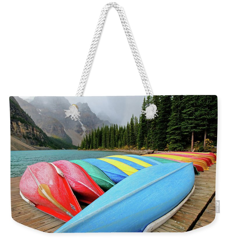 Scenics Weekender Tote Bag featuring the photograph Canoes Line Dock At Moraine Lake, Banff by Wildroze