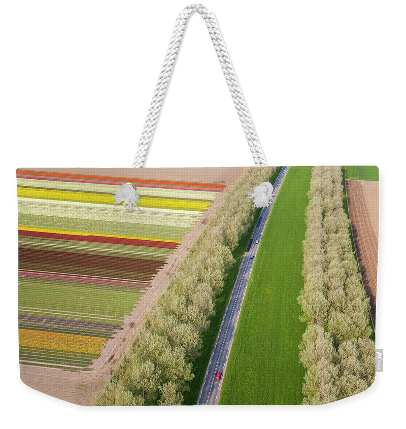 Scenics Weekender Tote Bag featuring the photograph Car On Road Near Tulip Fields, Holland by Peter Adams