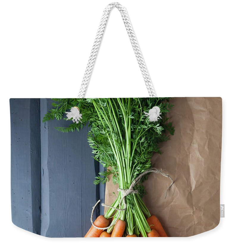 Bunch Weekender Tote Bag featuring the photograph Carrots With Brown Paper On Wooden by Westend61