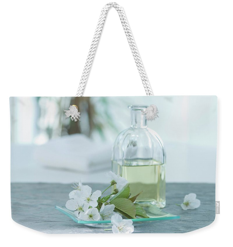 Spa Weekender Tote Bag featuring the photograph Cherry Blossom With Aroma Oil, Close Up by Westend61
