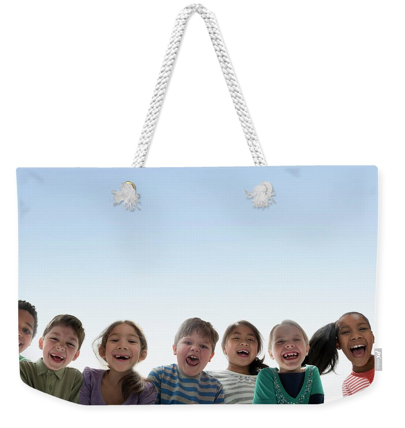 Asian And Indian Ethnicities Weekender Tote Bag featuring the photograph Children Smiling Together Outdoors by Jose Luis Pelaez Inc
