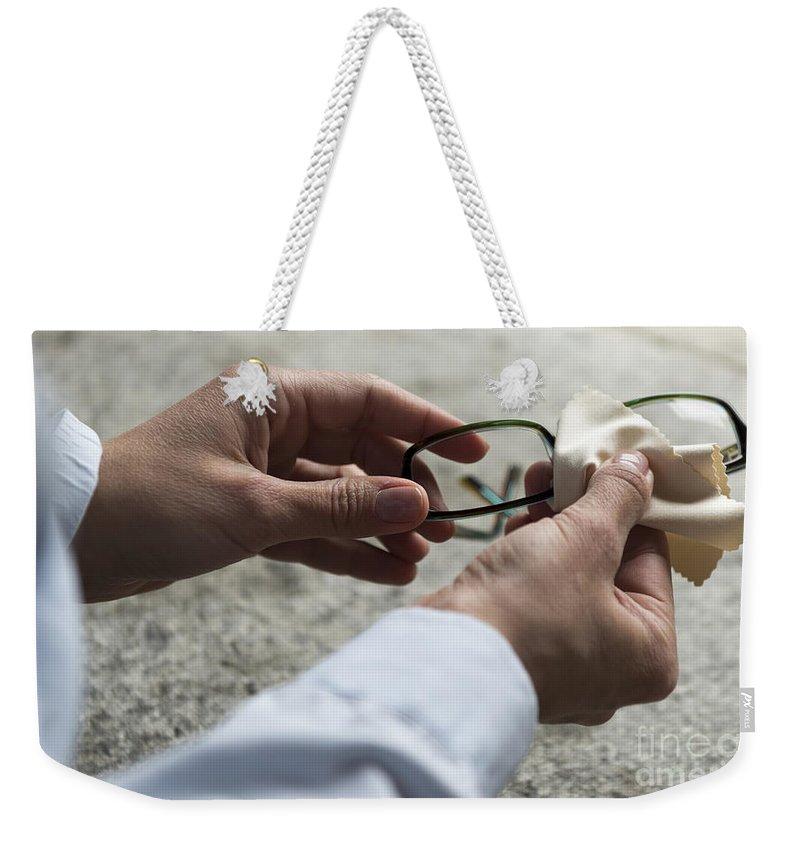 Eyeglasses Weekender Tote Bag featuring the photograph Cleaning Her Eyeglasses by Mats Silvan