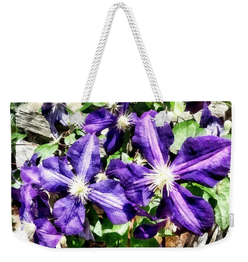 Clematis Weekender Tote Bag featuring the photograph Clematis On A Stone Wall by Susan Savad