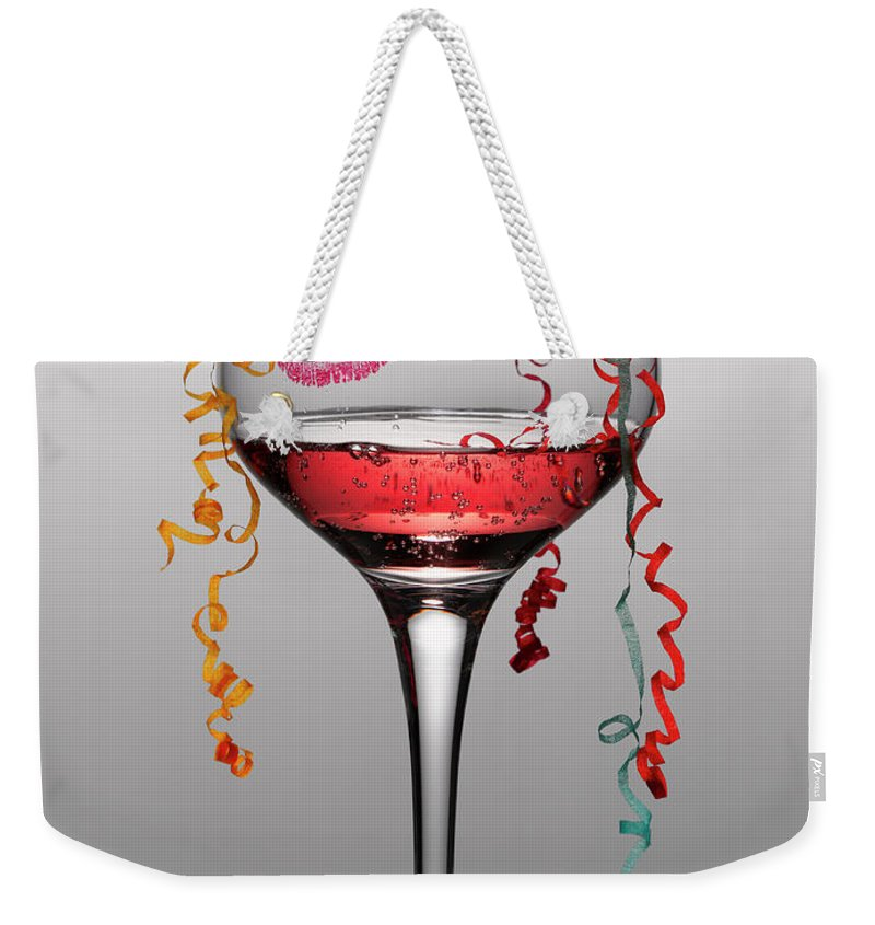 Streamer Weekender Tote Bag featuring the photograph Confetti Hanging From Glass Of Pink by Andy Roberts