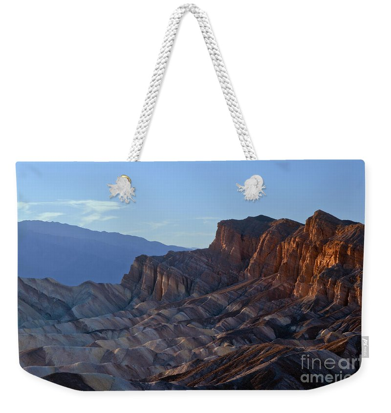 Zabriskie Point Death Valley National Park California Parks Mountain Mountains Desert Desert Ridge Ridges Light And Shadow Shadows Peak Peaks Sand Rock Landscape Landscapes Desertscape Desertscapes Daybreak Weekender Tote Bag featuring the photograph Creeping Rays Of Sun by Bob Phillips