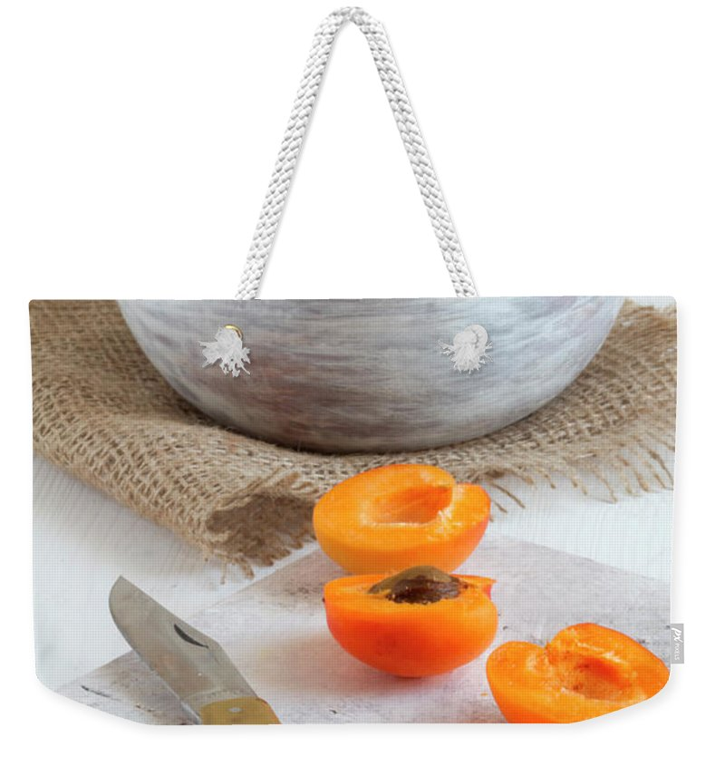 Cutting Board Weekender Tote Bag featuring the photograph Cross Section Apricots With Knife And by Westend61