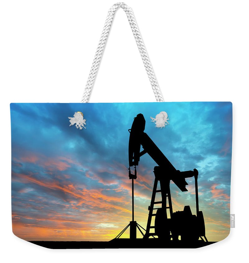 Shadow Weekender Tote Bag featuring the photograph Dawn Over Petroleum Pump by Grafissimo