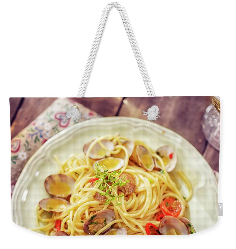 Italian Food Weekender Tote Bag featuring the photograph Delicious Spaghetti Alla Vongole Served by Gmvozd