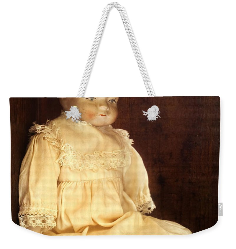 Antique; Childhood; Dirty; Doll; Alone; Shelf; Dress; Eyes; Face; Gazing; Heirloom; Nostalgia; Old; Staring; Toy; Vintage; Dark; Creepy; Female; Porcelain; Girl; Lace; Socks Weekender Tote Bag featuring the photograph Doll Shop by Margie Hurwich