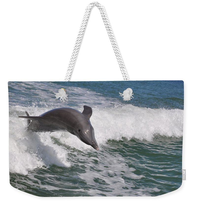 Landscapes Weekender Tote Bag featuring the photograph Dolphin Riding The Waves by Deborah Good