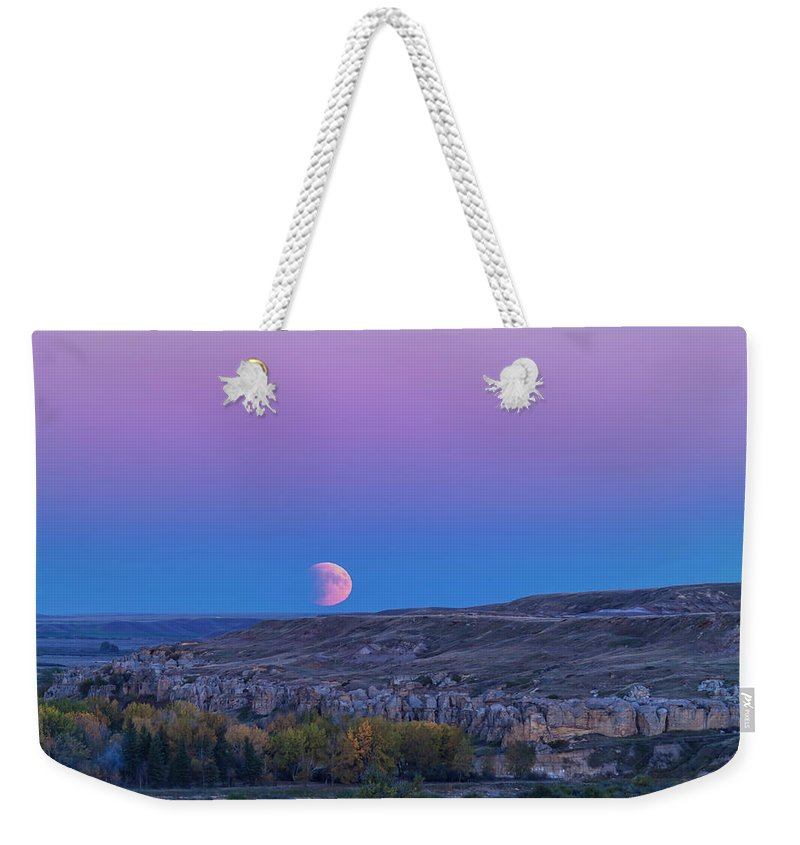 Alberta Weekender Tote Bag featuring the photograph Eclipse Moonrise At Writing-on-stone by Alan Dyer