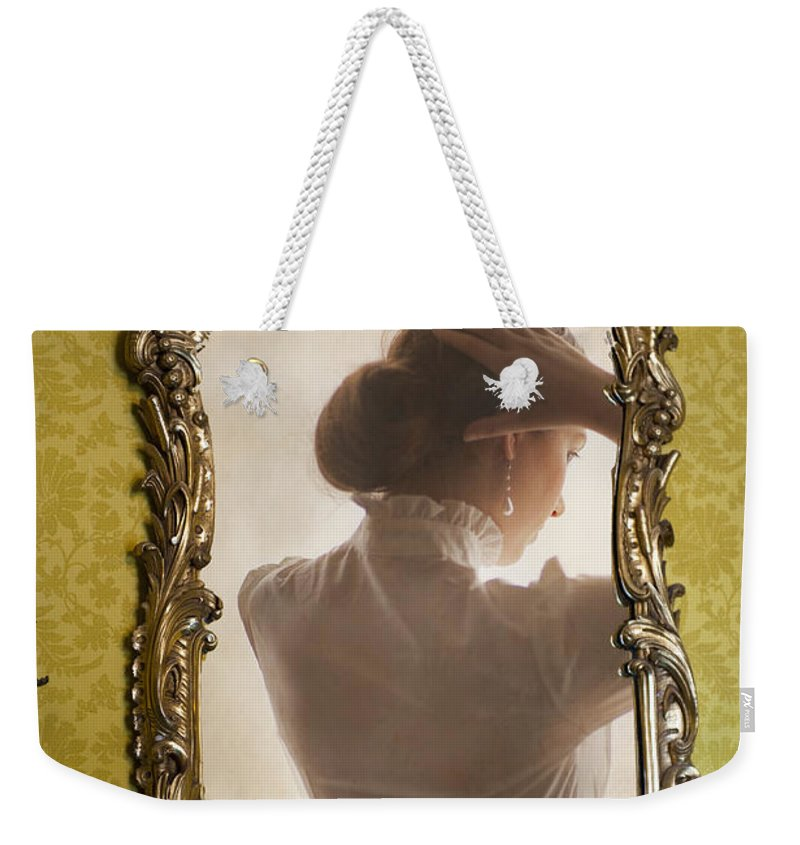 Edwardian Weekender Tote Bag featuring the photograph Edwardian Woman Styling Her Hair In The Mirror by Lee Avison