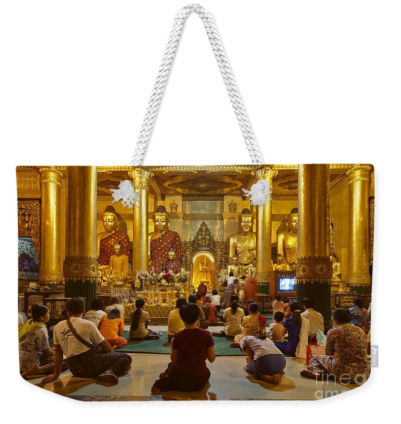 Myanmar Weekender Tote Bag featuring the photograph faithful Buddhists praying at Buddha Statues in SHWEDAGON PAGODA Yangon Myanmar by Juergen Ritterbach