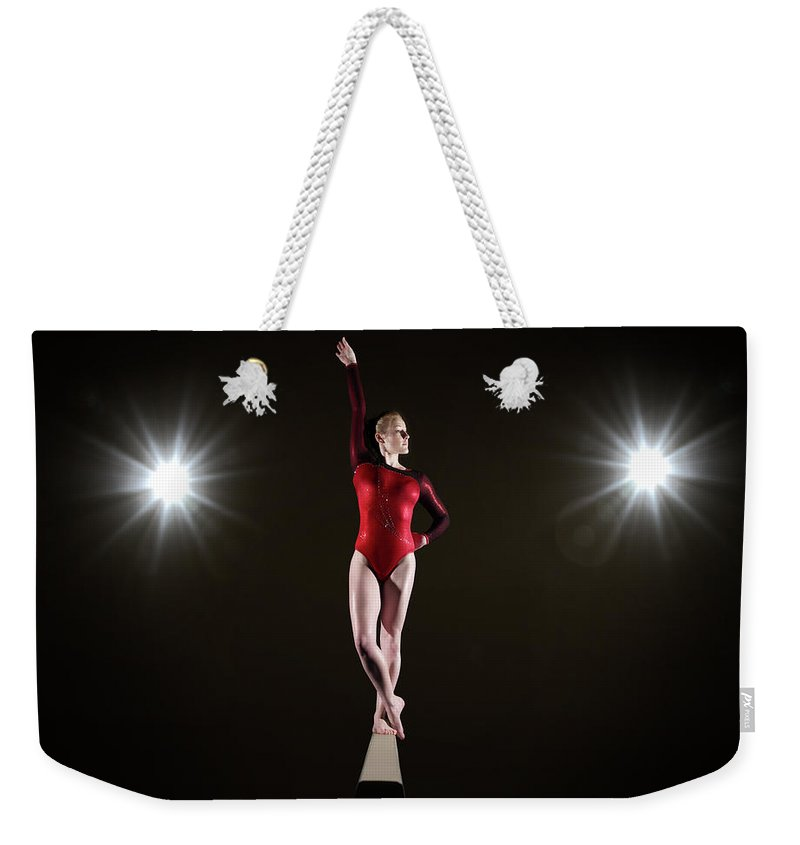 Human Arm Weekender Tote Bag featuring the photograph Female Gymnast On Balancing Beam by Mike Harrington