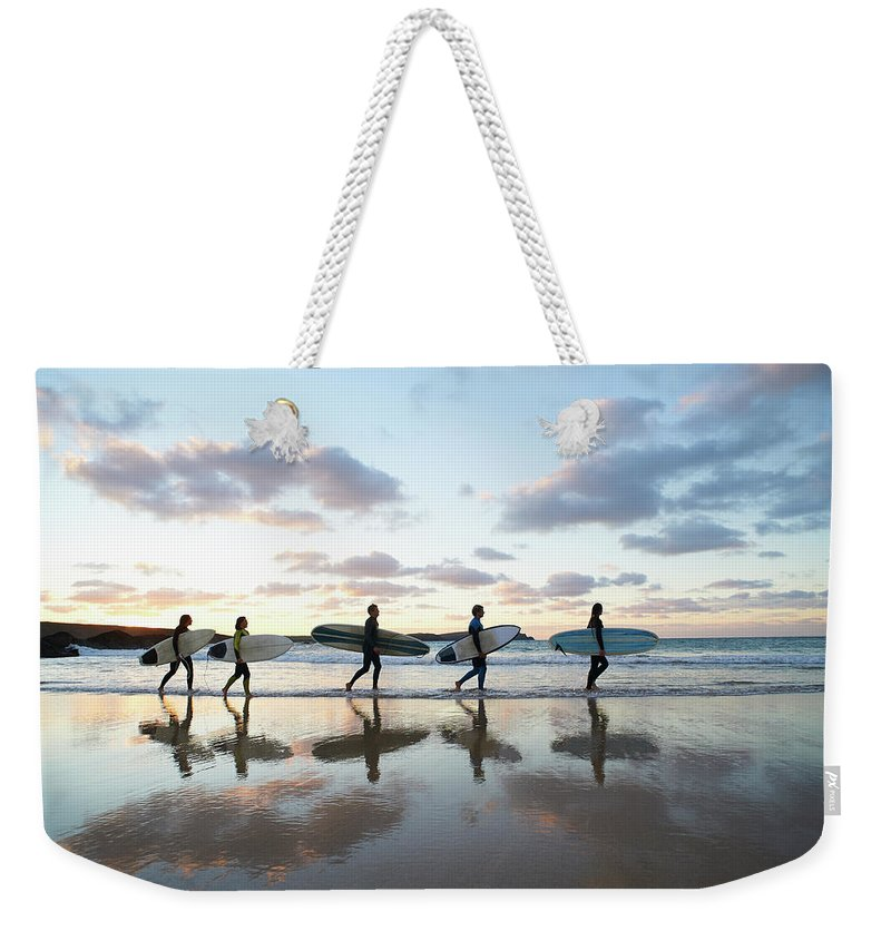 Young Men Weekender Tote Bag featuring the photograph Five Surfers Walk Along Beach With Surf by Dougal Waters