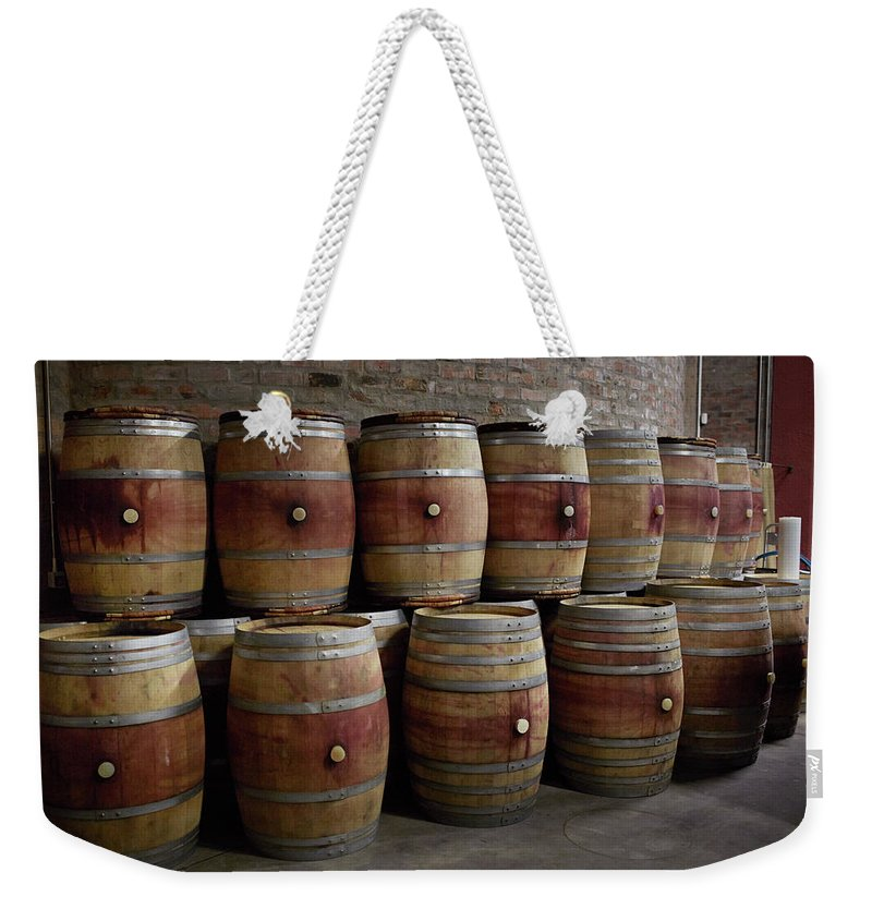 Stellenbosch Weekender Tote Bag featuring the photograph French Wine Barrels Stacked At Winery by Klaus Vedfelt