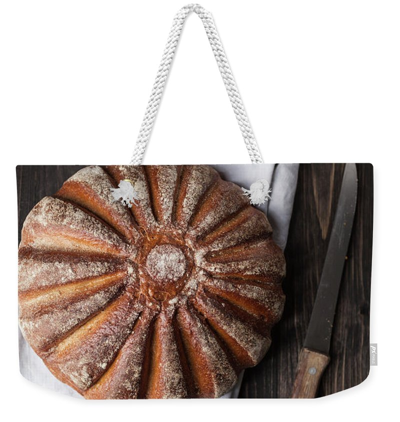 Kitchen Knife Weekender Tote Bag featuring the photograph Fresh Baked Bread With Kitchen Knife On by Westend61