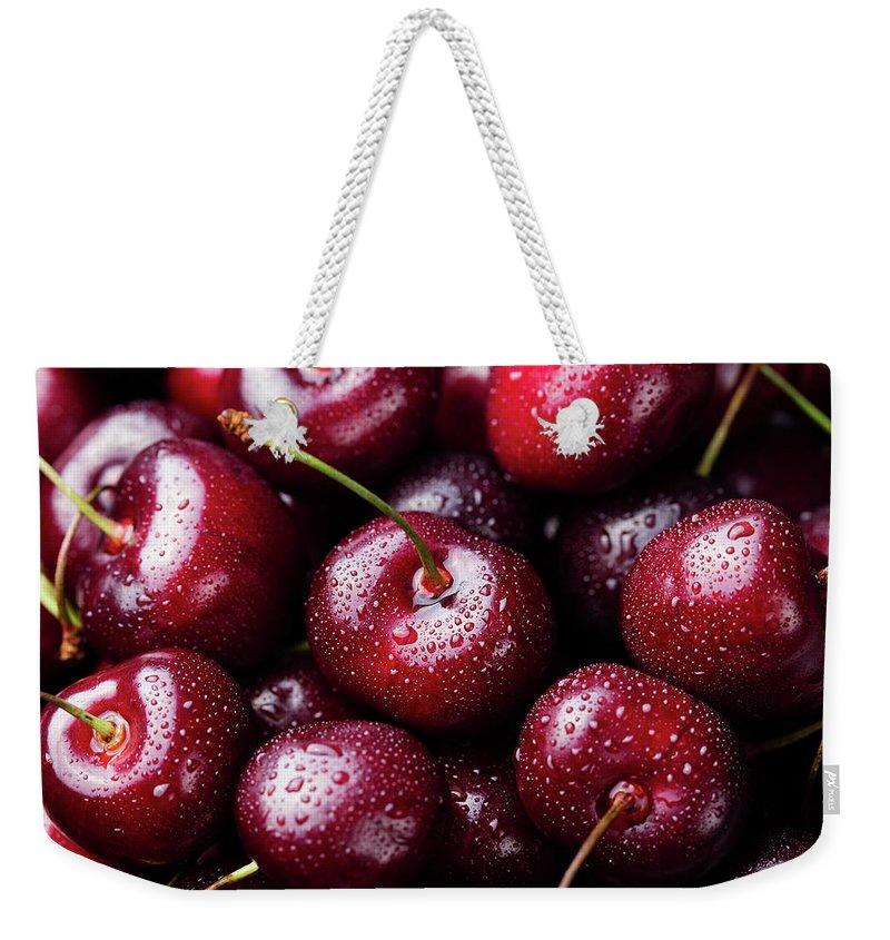 Cherry Weekender Tote Bag featuring the photograph Fresh Ripe Black Cherries Background by Anna Pustynnikova