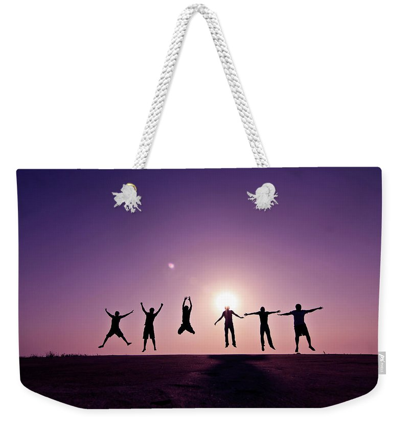 Human Arm Weekender Tote Bag featuring the photograph Friends Jumping Against Sunset by Kazi Sudipto Photography